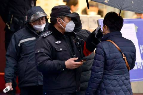 A policeman wearing a face mask takes a tourist's temperature at the Qinhuai scenic zone in Nan ...