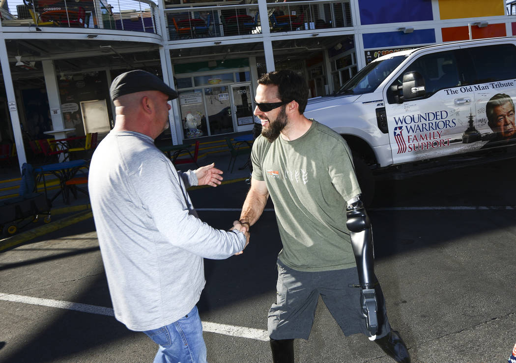 Rick Harrison, left, greets Navy veteran and Purple Heart recipient Andrew Bottrell, who was gi ...