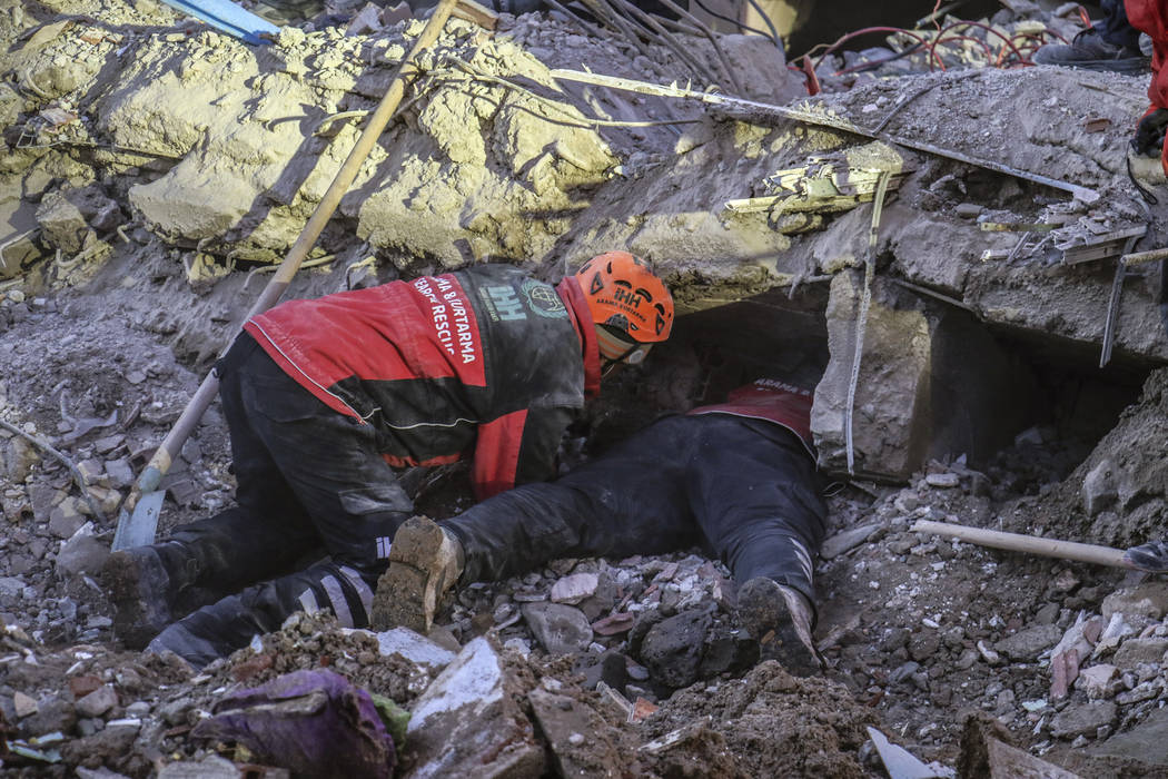 Rescue workers try to save people trapped under debris following a strong earthquake that destr ...