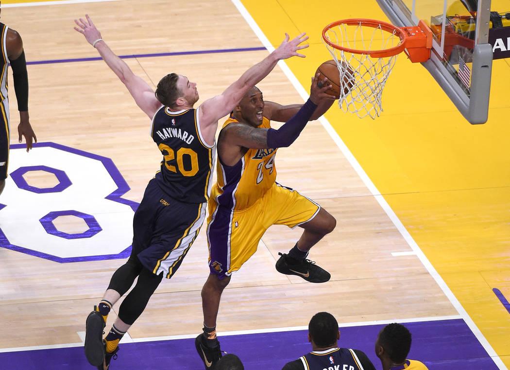 Los Angeles Lakers forward Kobe Bryant, right, shoots as Utah Jazz forward Gordon Hayward defen ...