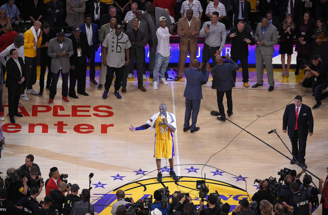 Los Angeles Lakers forward Kobe Bryant speaks to fans as friends and former teammates stand beh ...