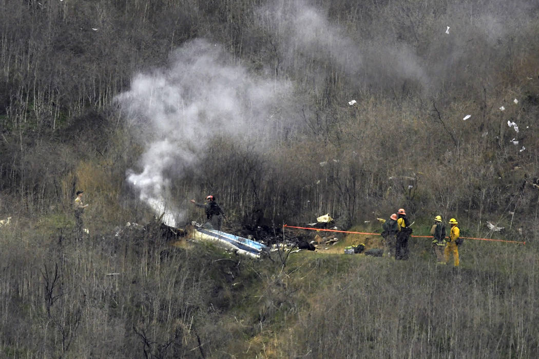 Firefighters work the scene of a helicopter crash Sunday, Jan. 26, 2020, in Calabasas, Calif. N ...
