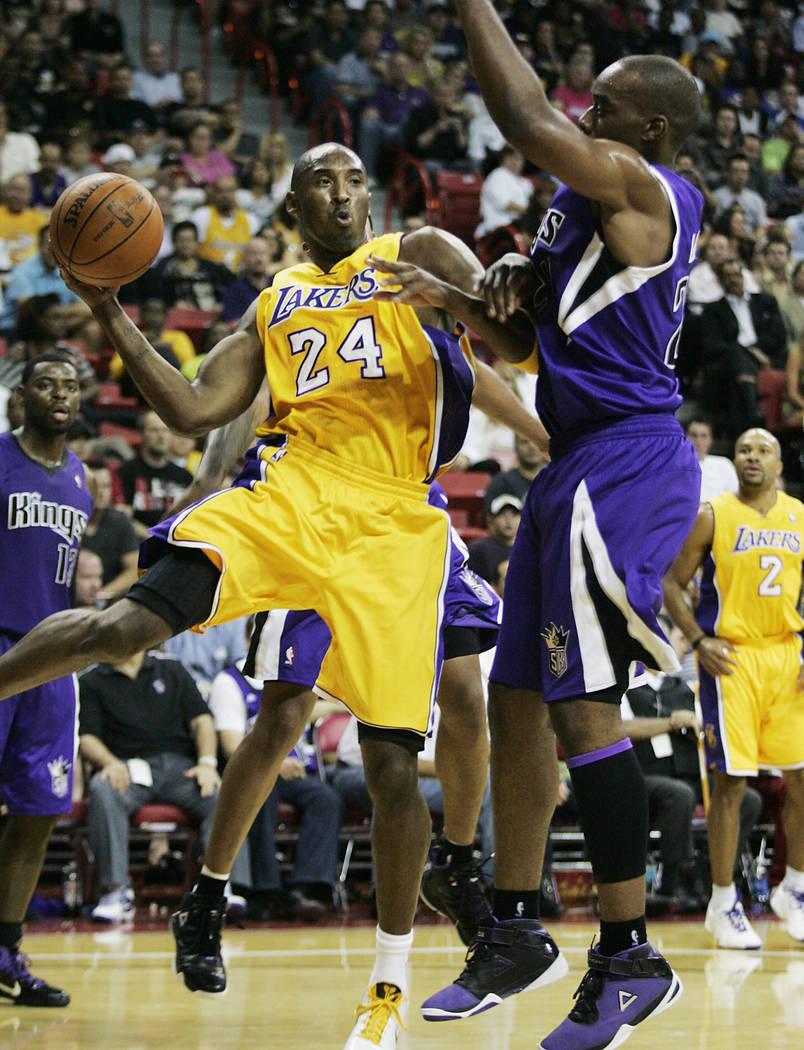 Los Angeles Lakers basketball star Kobe Bryant (24) looks to pass around Sacramento Kings playe ...