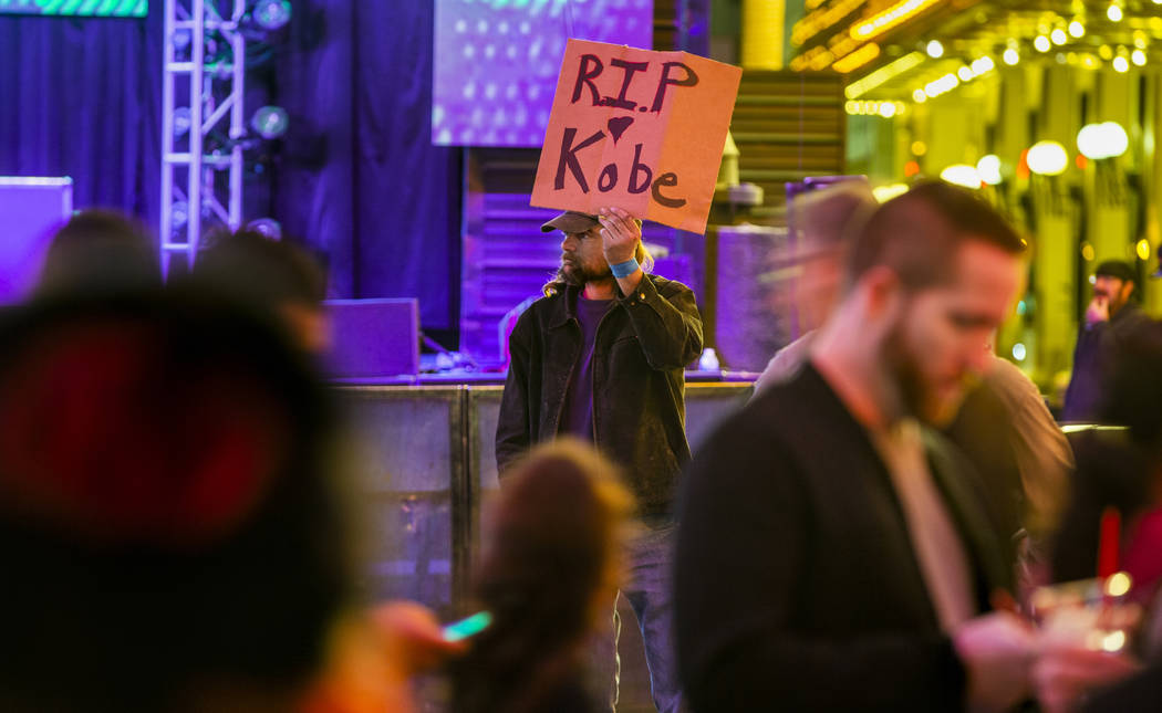 Aaron Young holds up a sign at the Fremont Street Experience as a memorial to Kobe Bryant follo ...