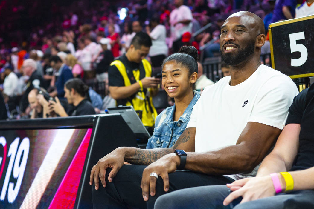 NBA legend Kobe Bryant sits with his daughter, Gianna, during the first half of the WNBA All-St ...