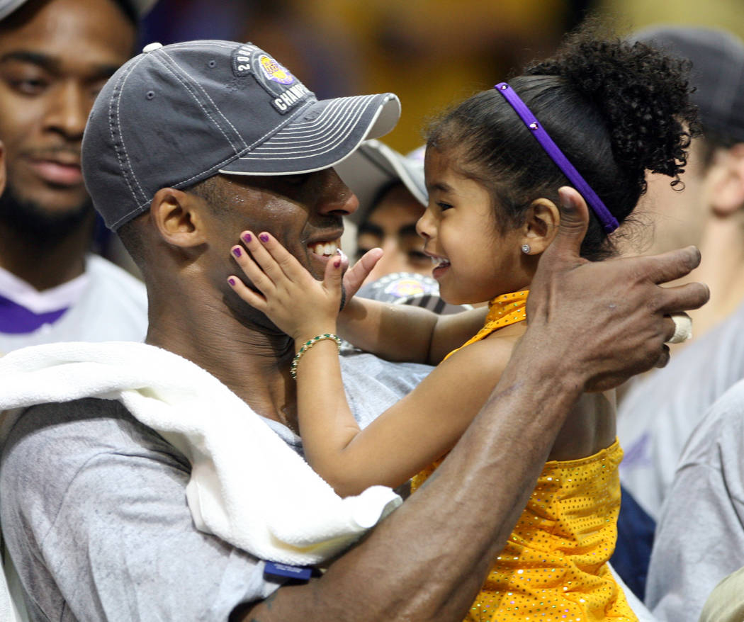 In this June 14, 2009, photo, Los Angles Lakers guard Kobe Bryant celebrates with his daughter ...