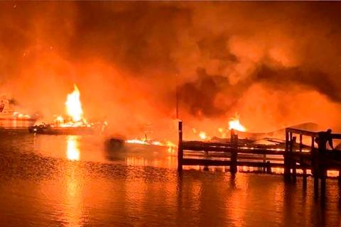 A fire burns on a dock where at least 35 vessels, many of them houseboats, were destroyed by fi ...