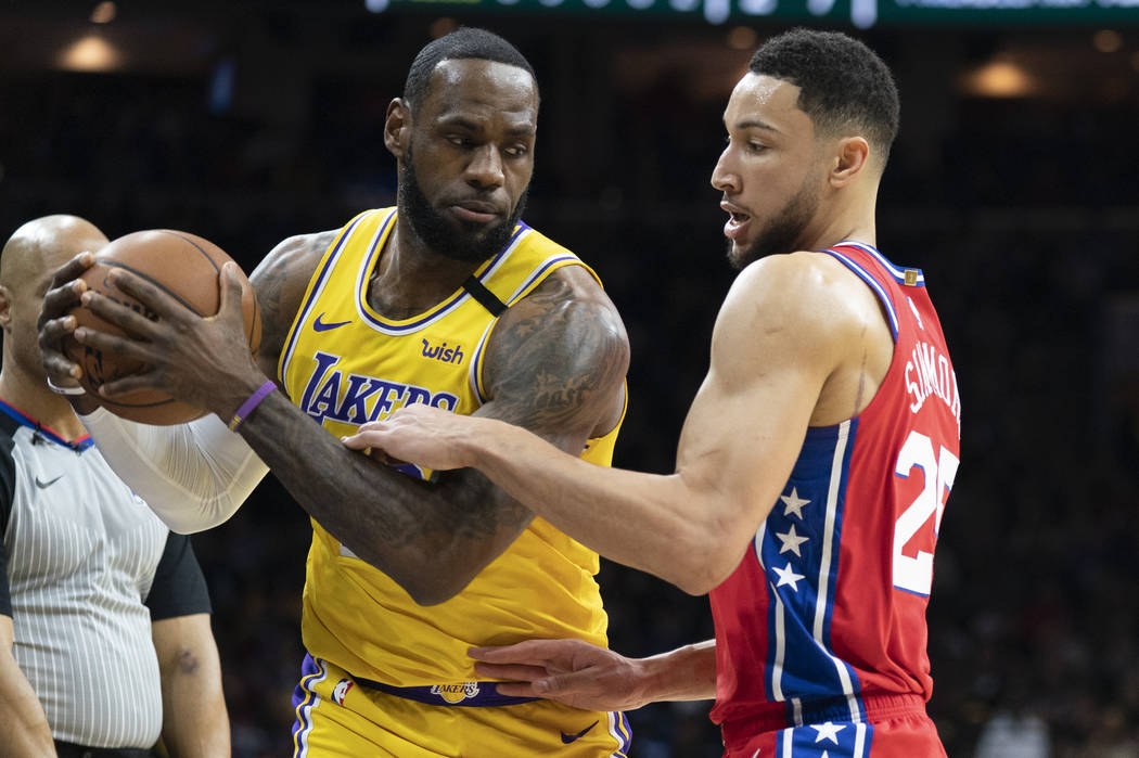 Los Angeles Lakers' LeBron James, left, tries to make his move on Philadelphia 76ers' Ben Simmo ...