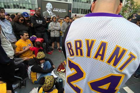 Fans mourn the loss of Kobe Bryant with makeshift memorials in front of La Live across from Sta ...