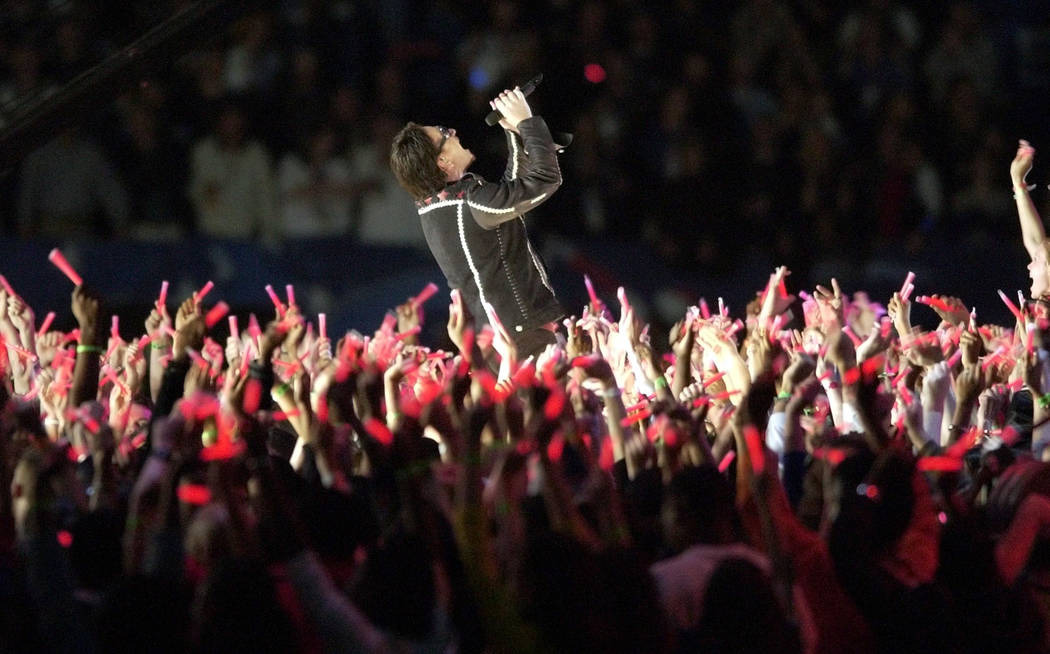 Bono performs amidst a sea of candles at halftime of Super Bowl XXXVI Sunday, Feb. 3, 2002 in N ...
