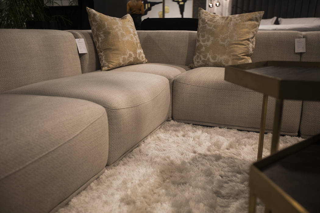 Neutral textures of the couches and rug show a coming trend for the year at the Sunpan booth at ...