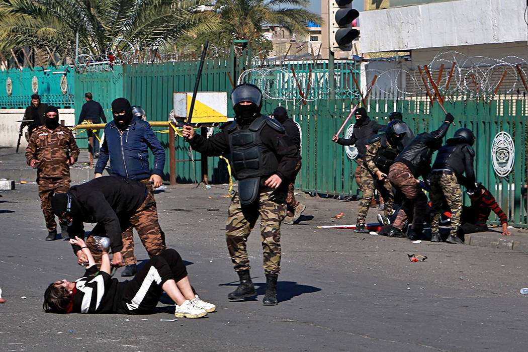 A riot policeman pins down a female anti-government protester to search her while security forc ...