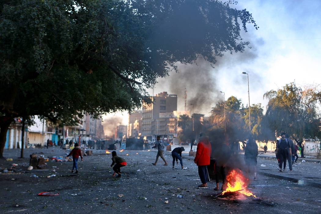 Protesters set fire to close a street during clashes between security forces and anti-governmen ...