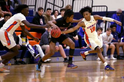 Durango guard Keshon Gilbert (10) moves the ball between Bishop Gorman guards Will McClendon (1 ...