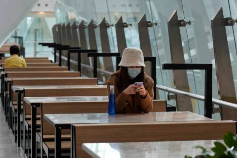 A woman wears protective face mask at the high speed train station in Hong Kong, Tuesday, Jan. ...