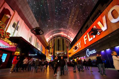 People watch the recently-upgraded Viva Vision screen at the Fremont Street Experience. A man l ...