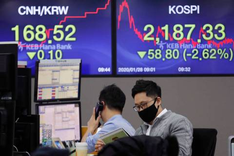 A currency trader wearing a mask watches a calendar at the foreign exchange dealing room of the ...