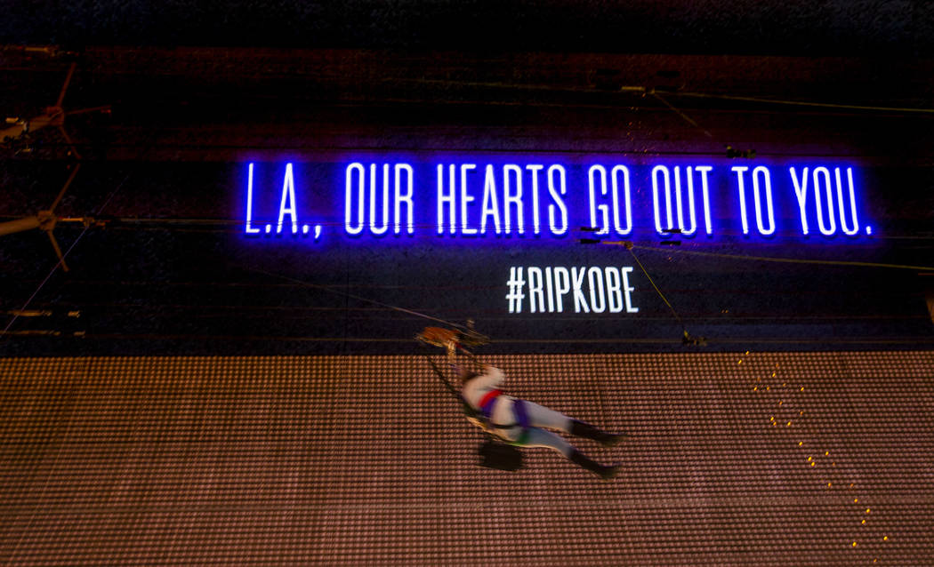 A SlotZilla Zipline rider moves past as the Fremont Street Experience offers sympathy to L.A. w ...