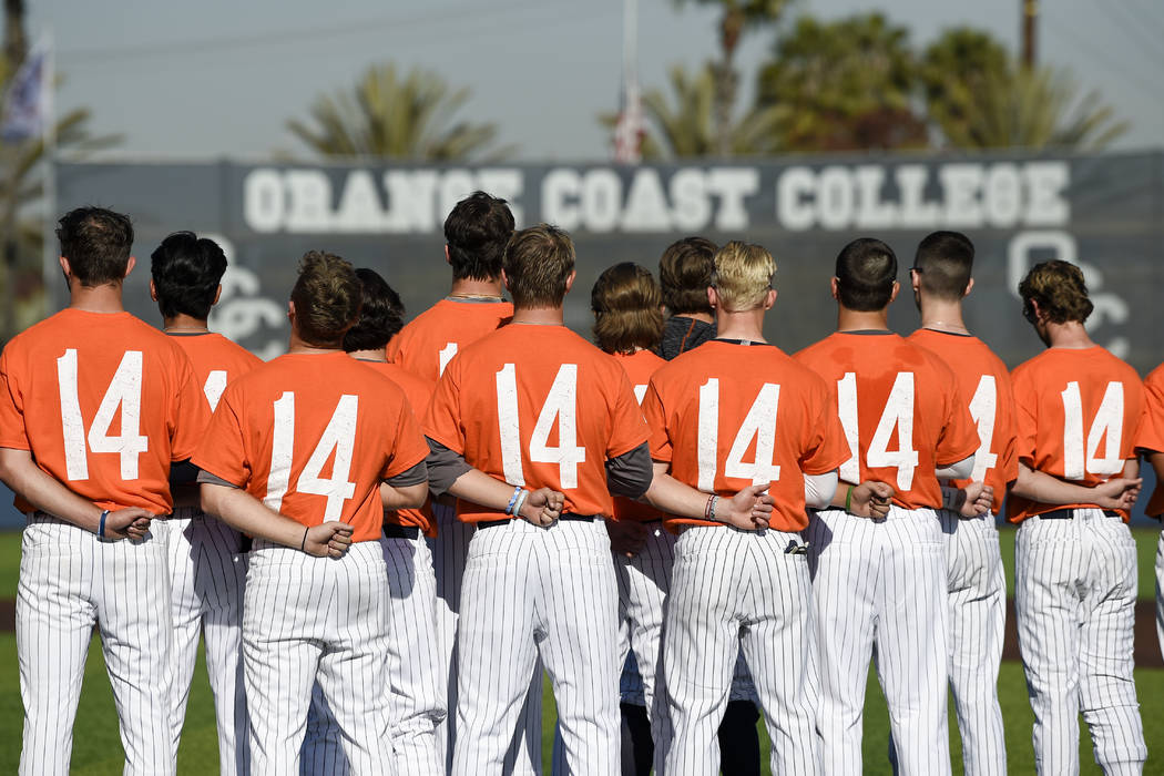 The Orange Coast College baseball players stands for the national anthem while wearing shirts w ...