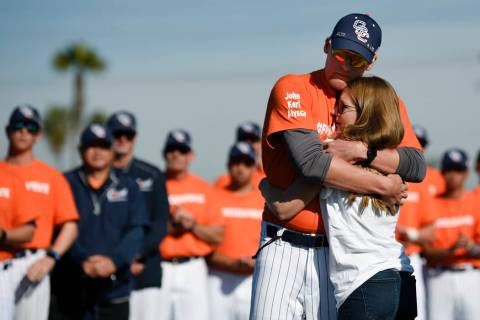 Associate coach Nate Johnson, left, embraces his wife Jonai during a ceremony held for John Alt ...