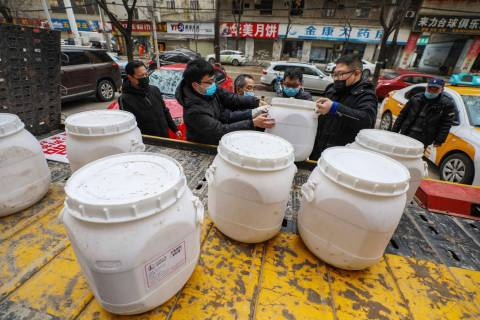 Workers unload canisters of disinfectant from a truck in Wuhan in central China's Hubei Provinc ...