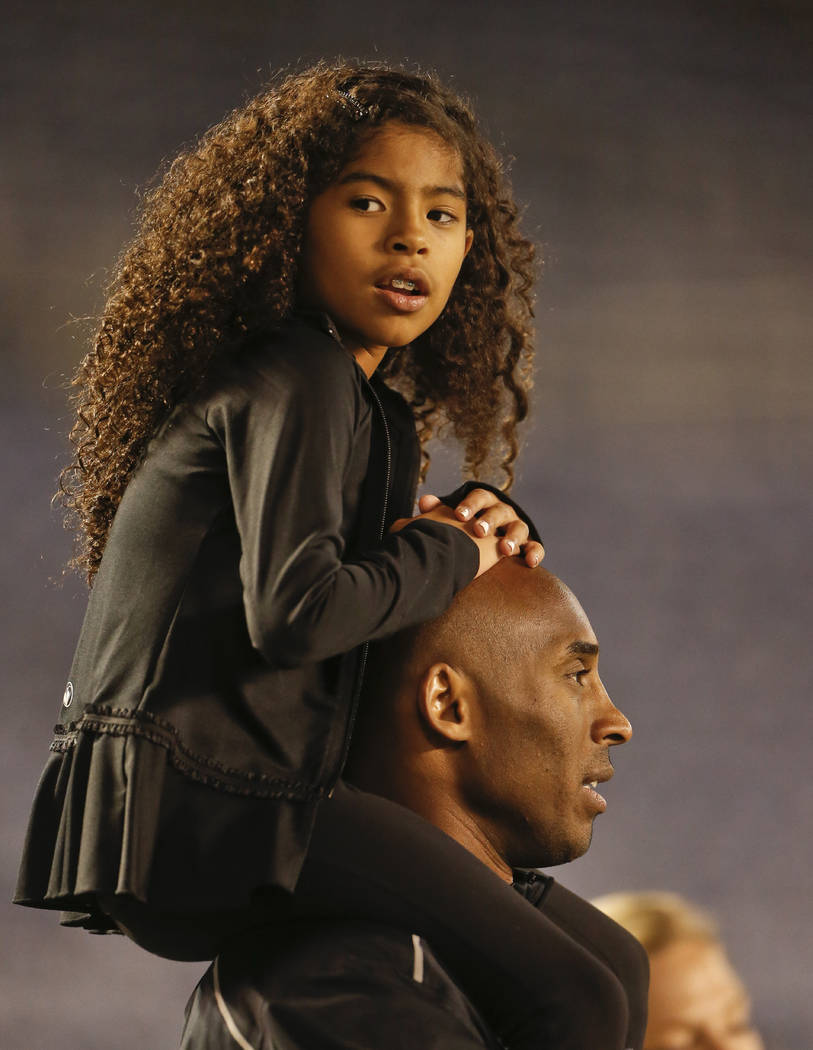 Gianna Maria-Onore Bryant sits on the shoulders of her father, Kobe, as they attend the women's ...