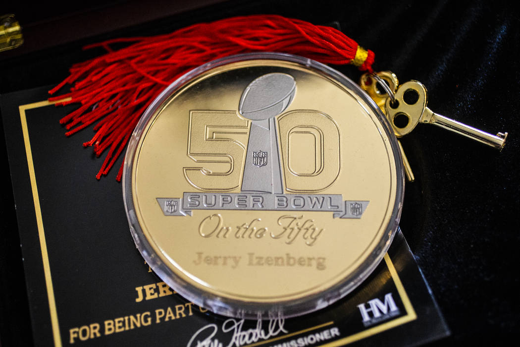 A coin celebrating long-time sports writer Jerry Izenberg's 50th Super Bowl at his home in Hend ...