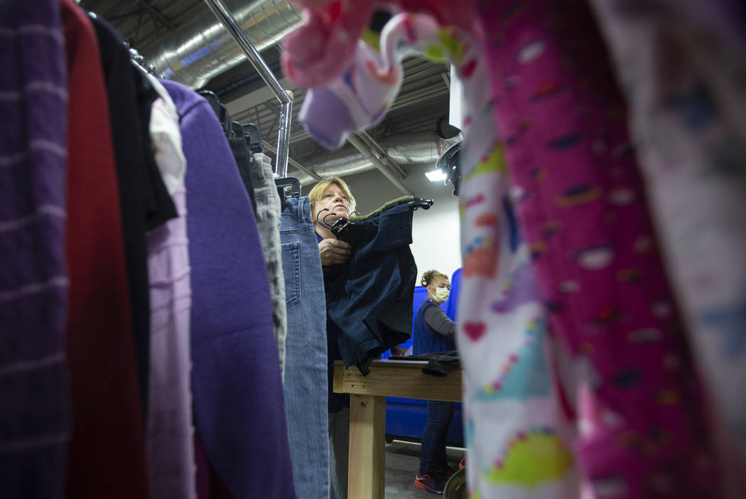 Linda Muth, top/left, sorts through donated clothing at Goodwill of Southern Nevada on Wednesda ...