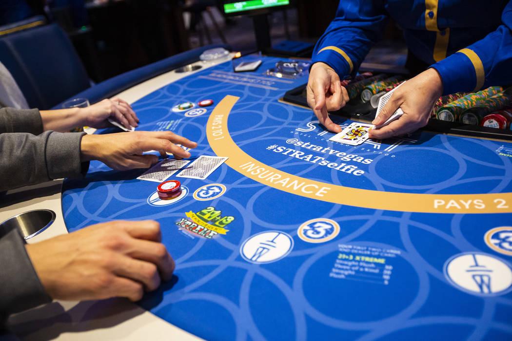 Blackjack dealer Amal Almisber, right, works the table as John and Shannon Welt, of Grants Pass ...