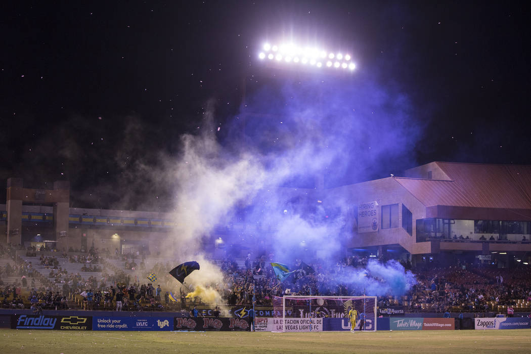 Fans cheer for a first half goal in the stands behind Las Vegas FC goalkeeper Thomas Olsen (30) ...