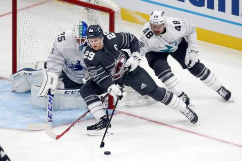 Colorado Avalanche forward Nathan MacKinnon (29) moves the puck against Vancouver Canucks goali ...