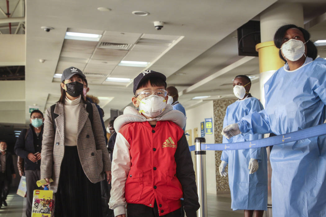 Passengers arriving from a China Southern Airlines flight from Changsha in China are screened f ...