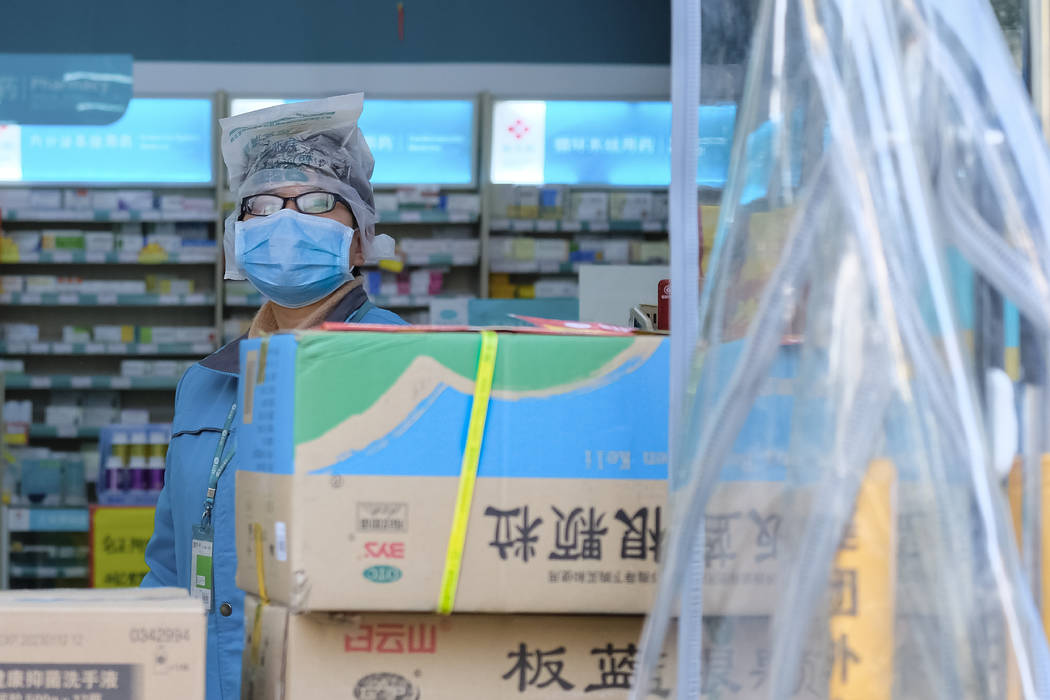A clerk wearing a face mask and a plastic bag stands in a pharmacy in Wuhan in central China's ...