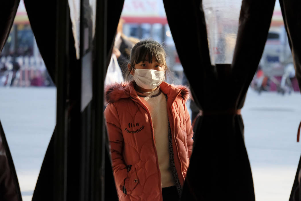 A girl wearing a face mask stands in the entrance to a shop in Wuhan in central China's Hubei P ...