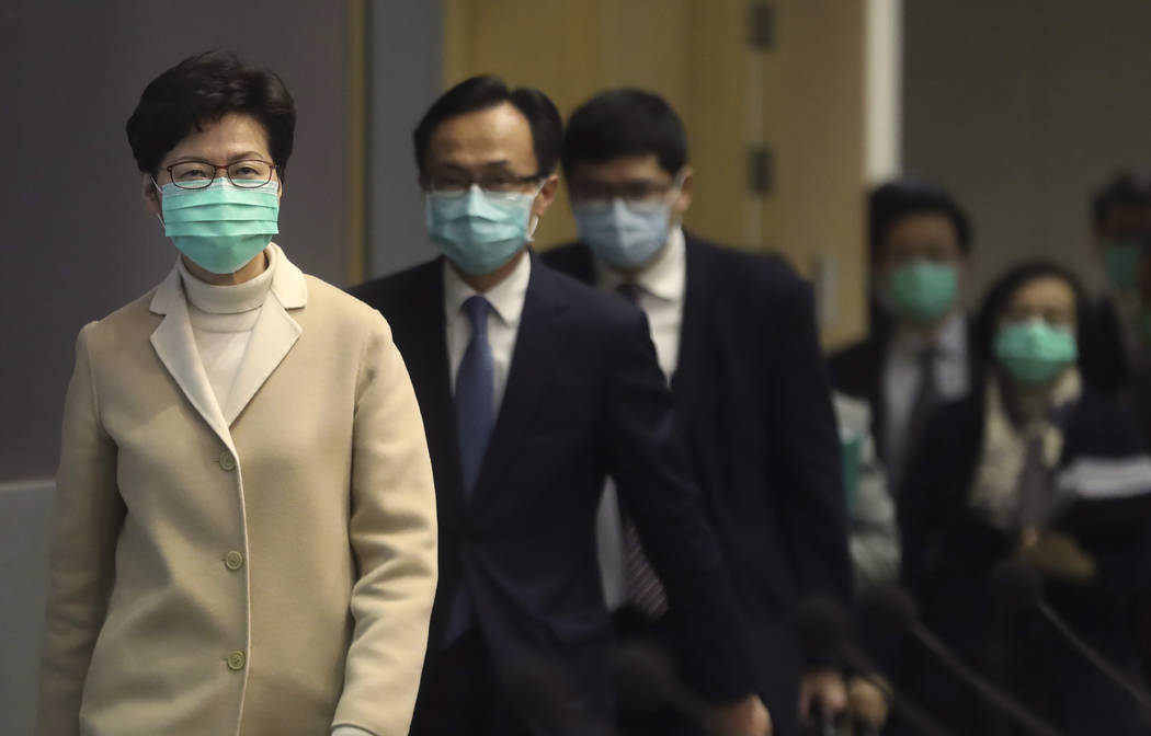 Hong Kong Chief Executive Carrie Lam, front, and other government officials wear protective fac ...