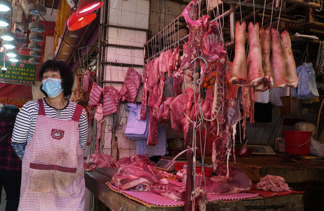A vendor wears a face mask selling meat at a market in Hong Kong, Friday, Jan. 31, 2020. The Wo ...