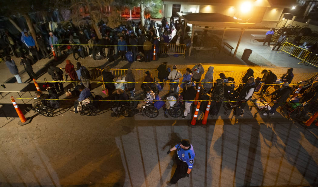 People wait in line to check in and get a sleeping mat at the Courtyard Homeless Resource Cente ...