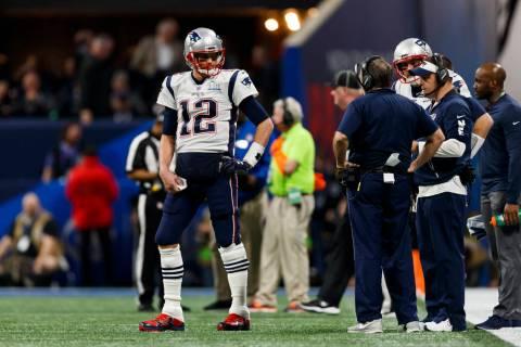 New England Patriots quarterback Tom Brady (12) talks to head coach Bill Belichick on the sidel ...