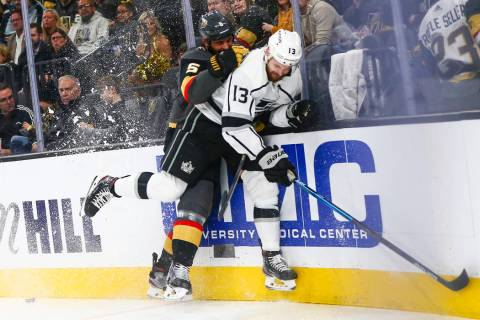 Golden Knights' Deryk Engelland (5) takes Los Angeles Kings' Kyle Clifford (13) to the boards d ...
