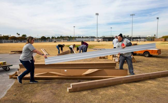 Employee volunteers from Health Plan of Nevada work to build new bleachers and goals for the so ...