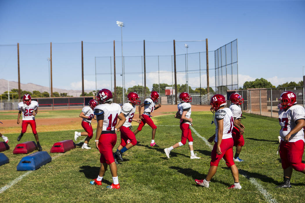 Players run through drills during footballl practice at the baseball field at Valley High Schoo ...