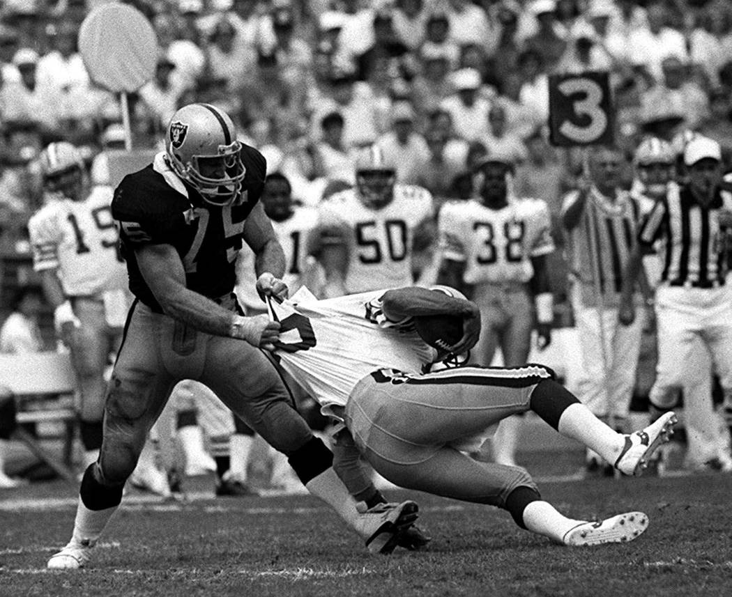 Los Angeles Raiders' Howie Long (75) takes down Green Bay Packers Randy Wright in Los Angeles, ...