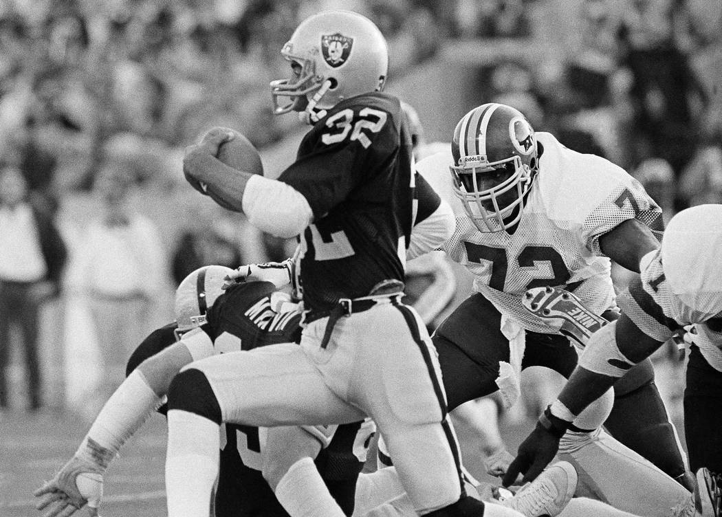 Los Angeles Raiders running back Marcus Allen runs with the ball after taking a handoff from qu ...