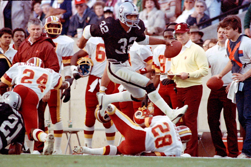 Los Angeles Raiders running back #32 Marcus Allen high steps his way down the sideline past Was ...