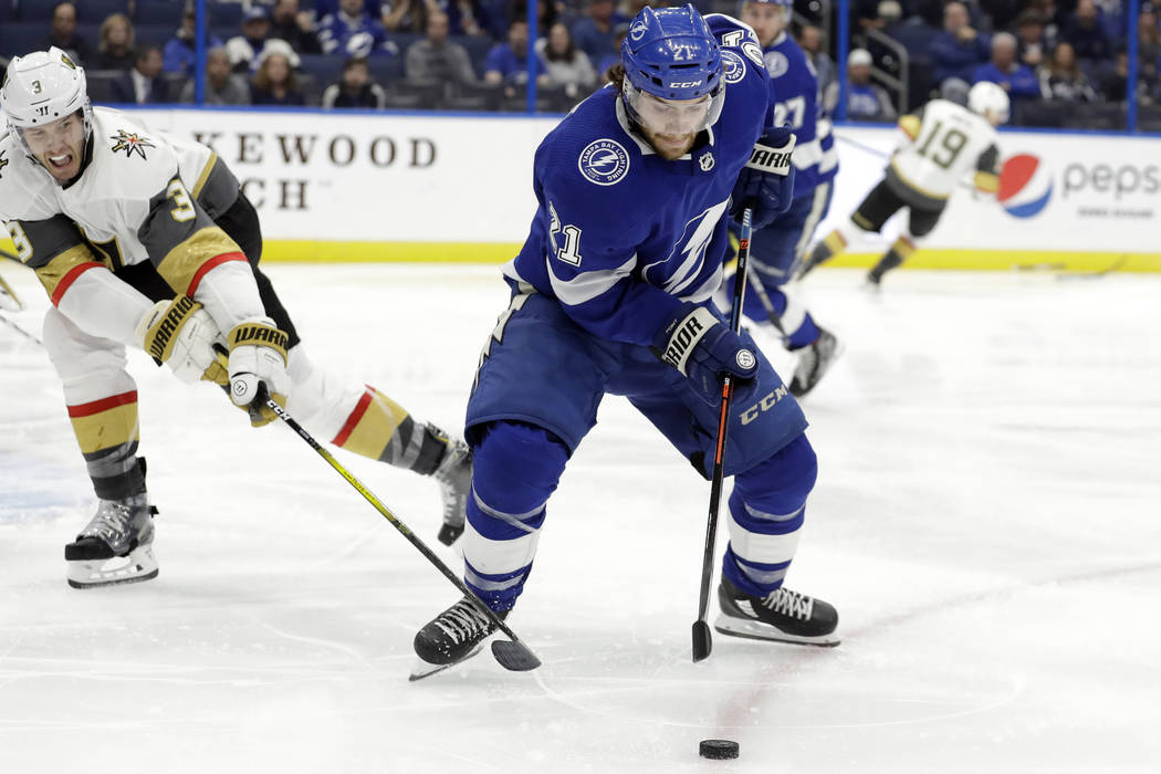 Tampa Bay Lightning center Brayden Point (21) loses the puck to a stick-check by Vegas Golden K ...