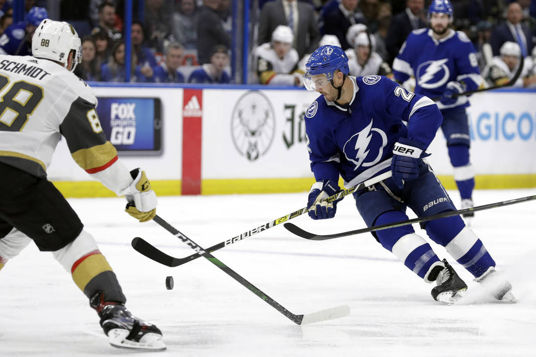 Tampa Bay Lightning defenseman Kevin Shattenkirk (22) tries to control a bouncing puck in front ...