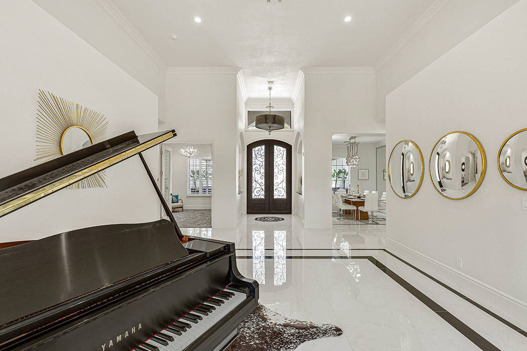 The living room has a piano. (Red Luxury Real Estate)
