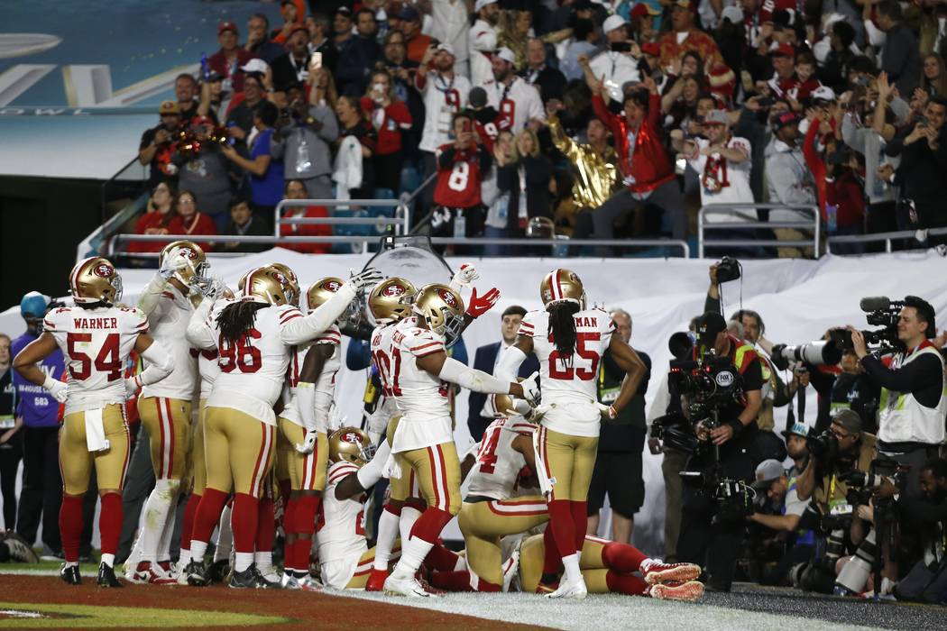 San Francisco 49ers players celebrate after Tarvarius Moore intercepted a pass against the Kans ...