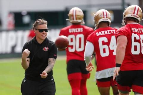 San Francisco 49ers offensive assistant coach Katie Sowers, left, tosses a ball to players duri ...