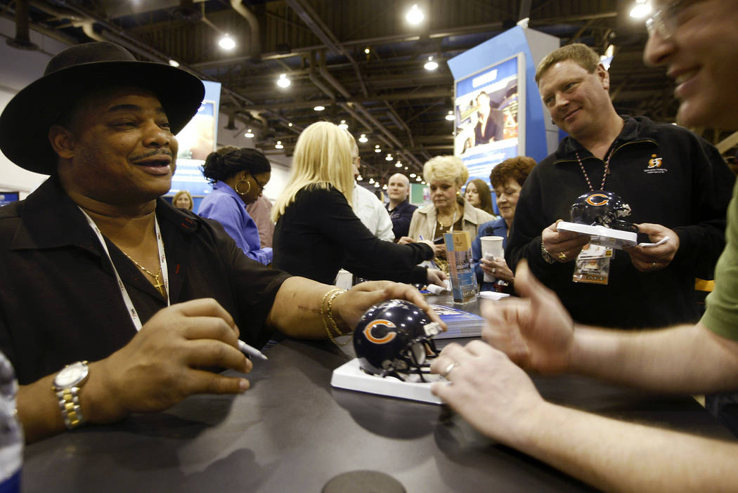 Former NFL football player with the Chicago Bear William 'The Refrigerator' Perry, left, signs ...
